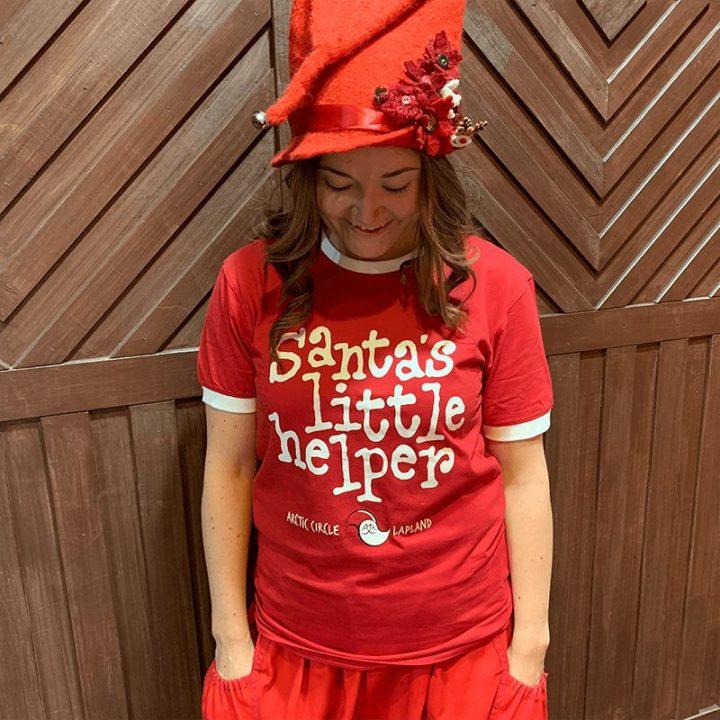 """Santa Claus Officen klassikko t-paita nyt saatavana kaikille Pukin pikku apureille! Punainen t-paita, jossa edessä painatus """"Santa's little helper"""". Materiaali 100% puuvilla. Tontun päällä."""