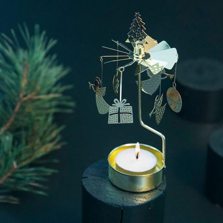 Rotary candle holder creates a cozy atmosphere and perfect as an interior detail. Just light the candle and watch the little metal christmas decoration figures rotate. Candle holder is gold-coloured and comes in a box. 1 tealight candle is included. Height approx.17cm. Great gift idea!